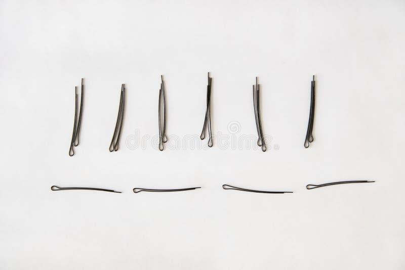 Μαύρα hairpins μετάλλων βρίσκονται οριζόντια και ακριβώς σε ένα άσπρο υπόβαθρο στοκ φωτογραφία