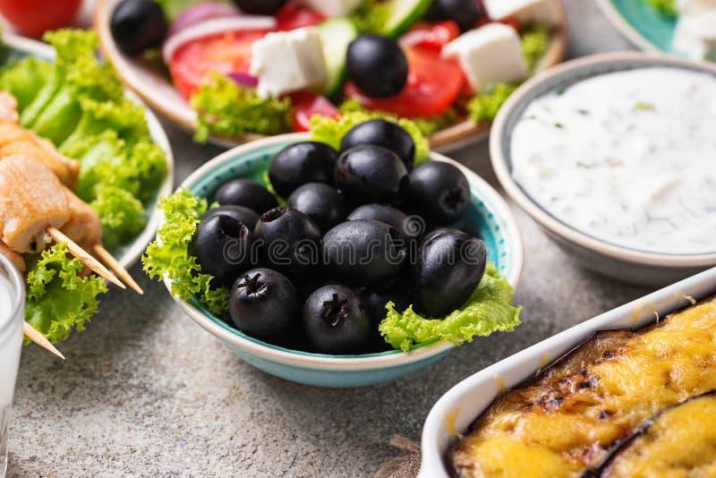 Μαύρες ελιές και παραδοσιακά ελληνικά πιάτα στοκ φωτογραφίες