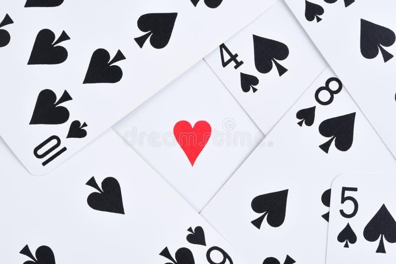 Μαύρες κάρτες παιχνιδιού που διασκορπίζονται σε έναν πίνακα με μια ενιαία κόκκινη καρδιά στοκ εικόνες