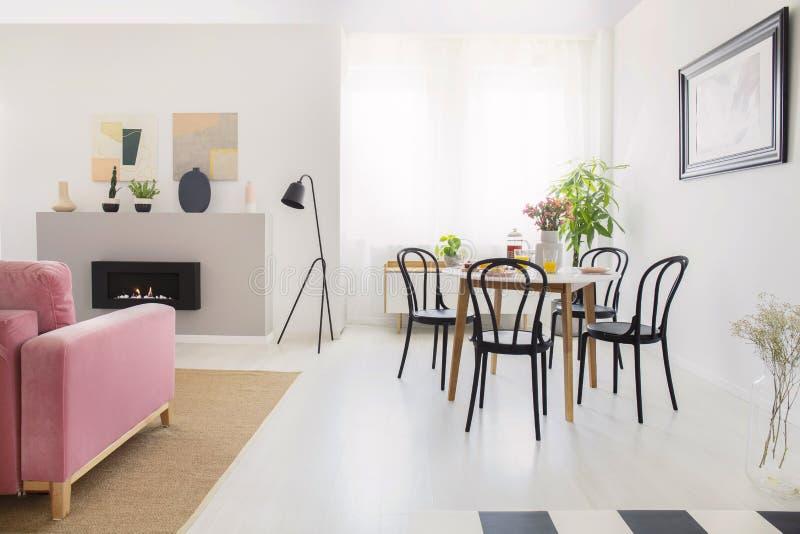 Μαύρες καρέκλες στον ξύλινο πίνακα στο άσπρο εσωτερικό διαμερισμάτων με το λαμπτήρα δίπλα στην εστία Πραγματική φωτογραφία στοκ εικόνες