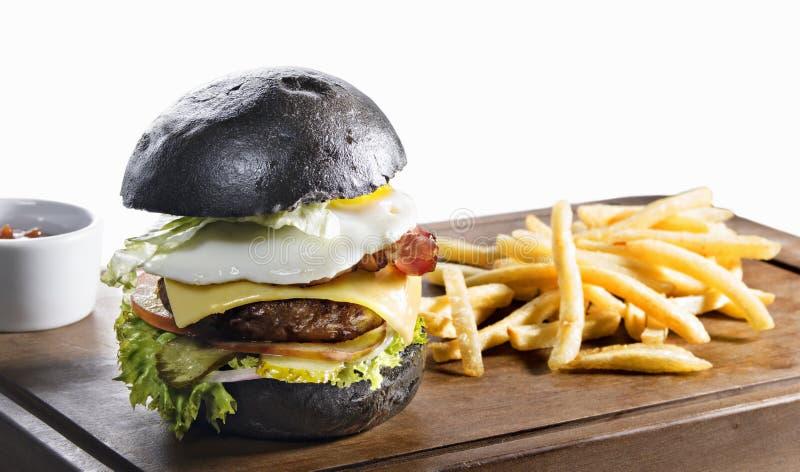 Μαύρες burger και τηγανιτές πατάτες που απομονώνονται στο λευκό στοκ φωτογραφία