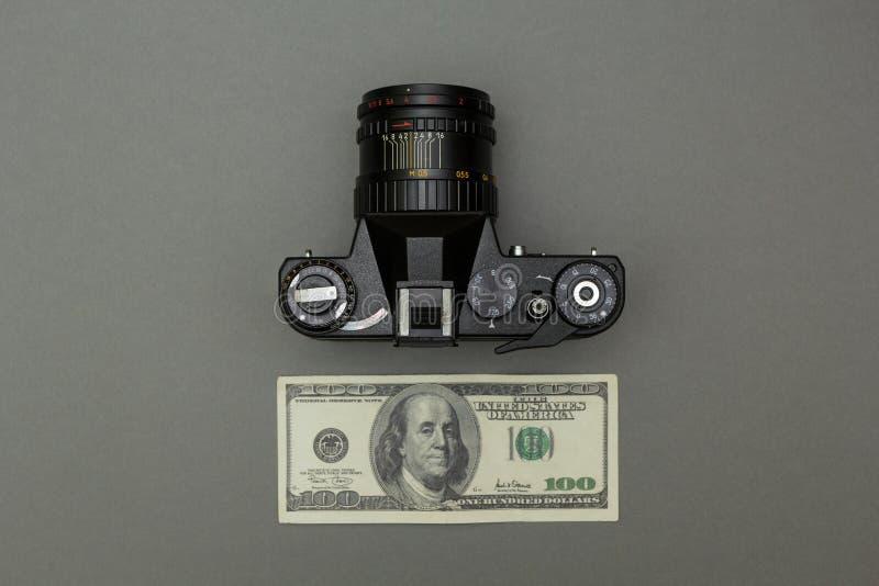 Μαύρη αναδρομική κάμερα και εκατό δολάρια σε ένα γκρίζο υπόβαθρο στοκ εικόνα με δικαίωμα ελεύθερης χρήσης