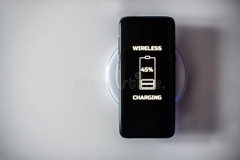 Μαύρη ασύρματη χρέωση smartphone οθονών επαφής στο φορτιστή επαγωγής στοκ εικόνες
