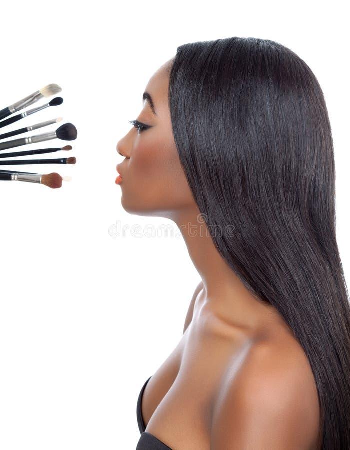 Μαύρη γυναίκα με την ευθείες τρίχα και makeup τις βούρτσες στοκ φωτογραφίες