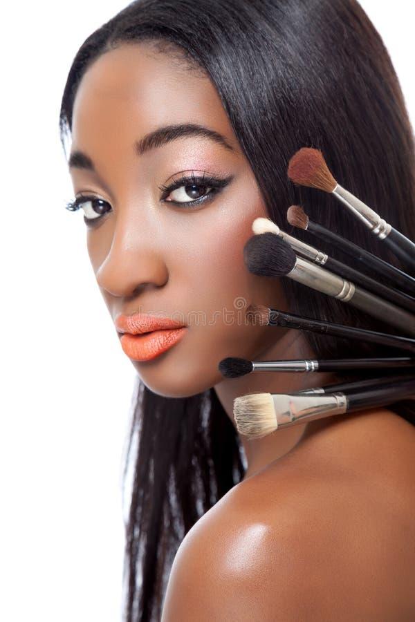 Μαύρη γυναίκα με την ευθείες τρίχα και makeup τις βούρτσες στοκ φωτογραφία με δικαίωμα ελεύθερης χρήσης