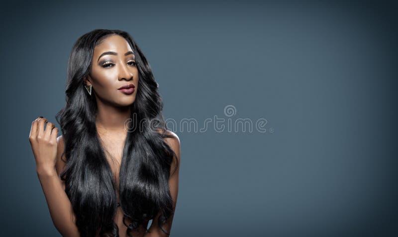 Μαύρη γυναίκα με τη μακριά πολυτελή λαμπρή τρίχα στοκ φωτογραφία