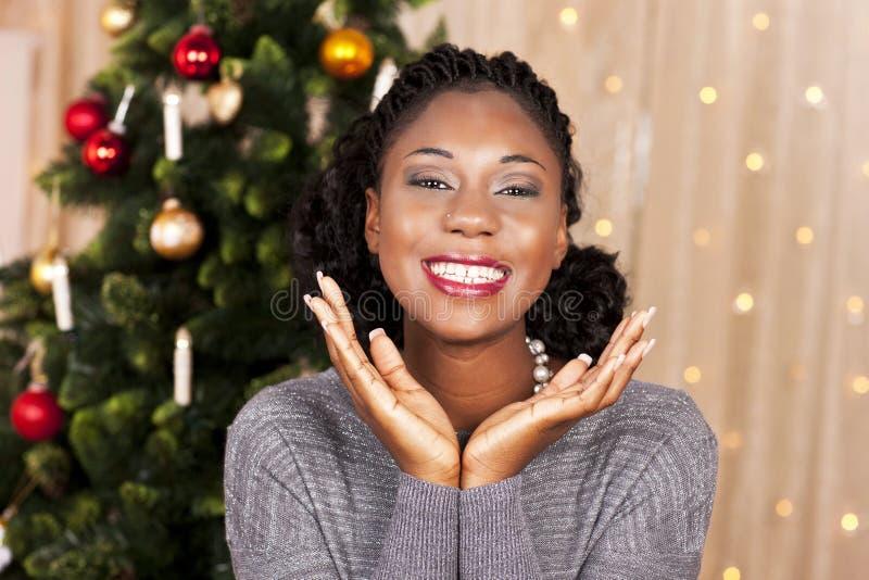 Μαύρη γυναίκα μπροστά από το χριστουγεννιάτικο δέντρο στοκ εικόνα με δικαίωμα ελεύθερης χρήσης