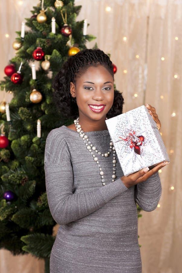 Μαύρη γυναίκα μπροστά από το χριστουγεννιάτικο δέντρο στοκ φωτογραφίες