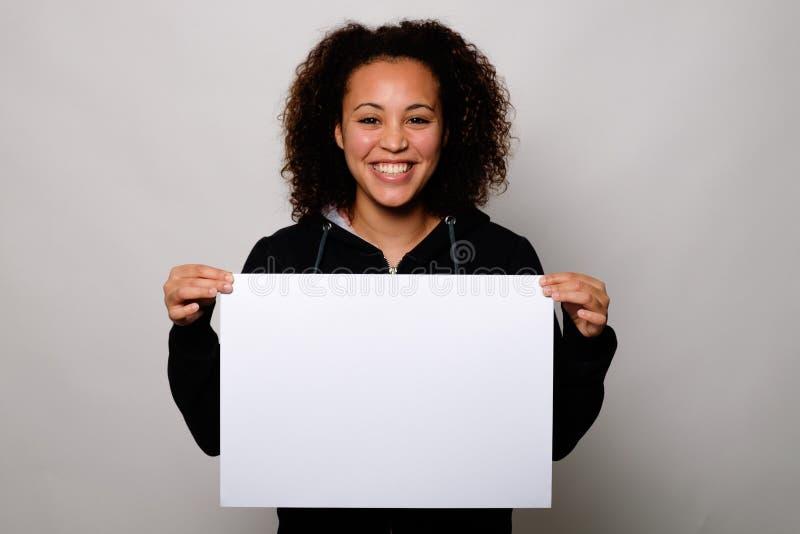 Μαύρη γυναίκα που επιδεικνύει το άσπρο έμβλημα στοκ φωτογραφίες