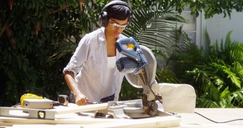 Μαύρη γυναίκα που κάνει την εγχώρια βελτίωση που μετρά το ξύλο στοκ φωτογραφία με δικαίωμα ελεύθερης χρήσης