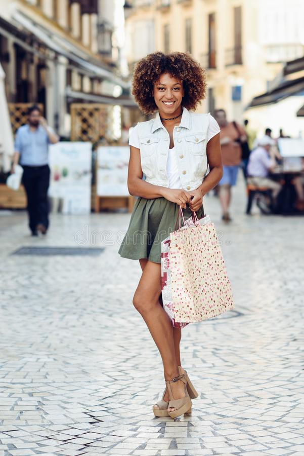 Μαύρη γυναίκα, afro hairstyle, με τις τσάντες αγορών στην οδό στοκ φωτογραφίες