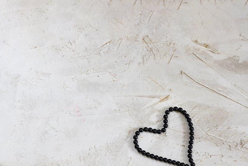 Μαύρη δαντέλλα χαντρών bijouterie ως καρδιά στην γκρίζα κατασκευασμένη επιφάνεια τσιμέντου, οριζόντια με το διάστημα αντιγράφων Ο στοκ εικόνες