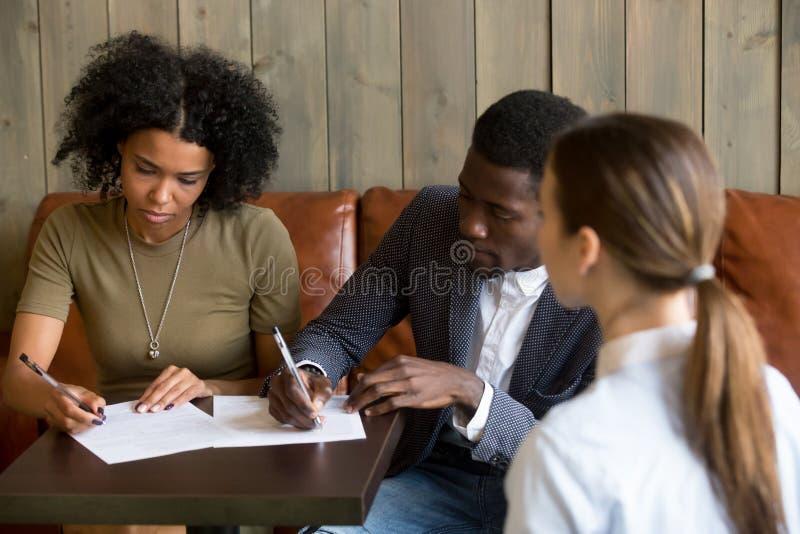 Μαύρη διαπραγμάτευση κλεισίματος ζευγών με την υπογραφή της σύμβασης στον καφέ στοκ εικόνα με δικαίωμα ελεύθερης χρήσης