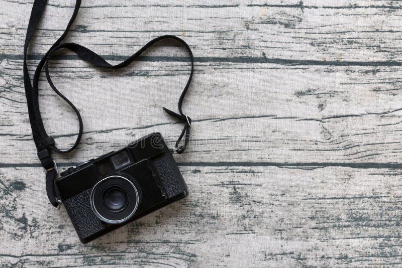 Μαύρη εκλεκτής ποιότητας κάμερα στο παλαιό ξύλινο υπόβαθρο τραπεζομάντιλων τυπωμένων υλών  στοκ εικόνες