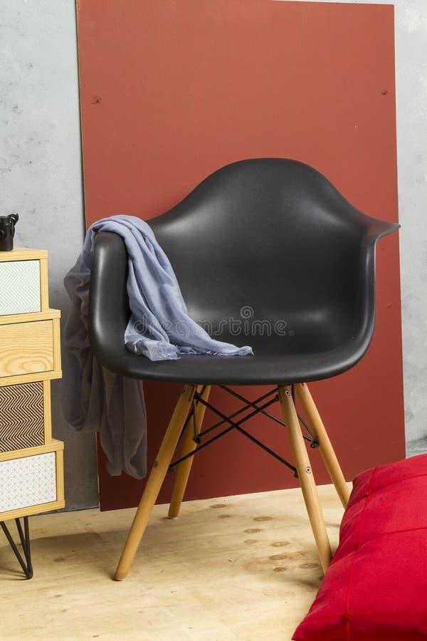 μαύρη καρέκλα με τα ξύλινα πόδια με τον μπλε τρόπο ζωής κουρελιών και το σκούρο παρτοκαλί υπόβαθρο στοκ φωτογραφία με δικαίωμα ελεύθερης χρήσης