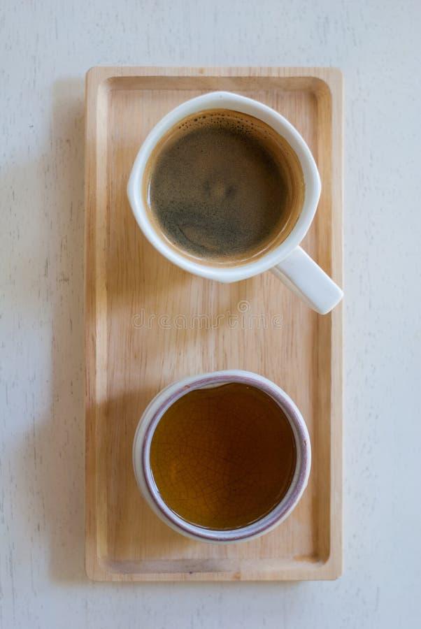 Μαύρη κούπα καφέ espresso με το λεπτό crema που τοποθετείται στον ξύλινο δίσκο με το γυαλί τσαγιού στοκ εικόνες με δικαίωμα ελεύθερης χρήσης