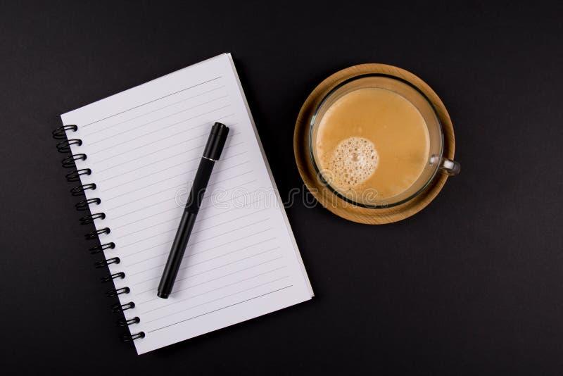 Μαύρη μάνδρα, σημειωματάριο, φλιτζάνι του καφέ σε έναν ξύλινο δίσκο, στο μαύρο πίνακα στοκ εικόνα με δικαίωμα ελεύθερης χρήσης
