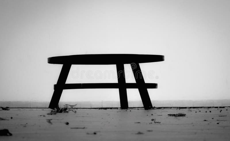 μαύρη μικρή καρέκλα στο πάρκο σε ένα ξύλινο πάτωμα, στον γκρίζο τοίχο υποβάθρου ελεύθερη απεικόνιση δικαιώματος