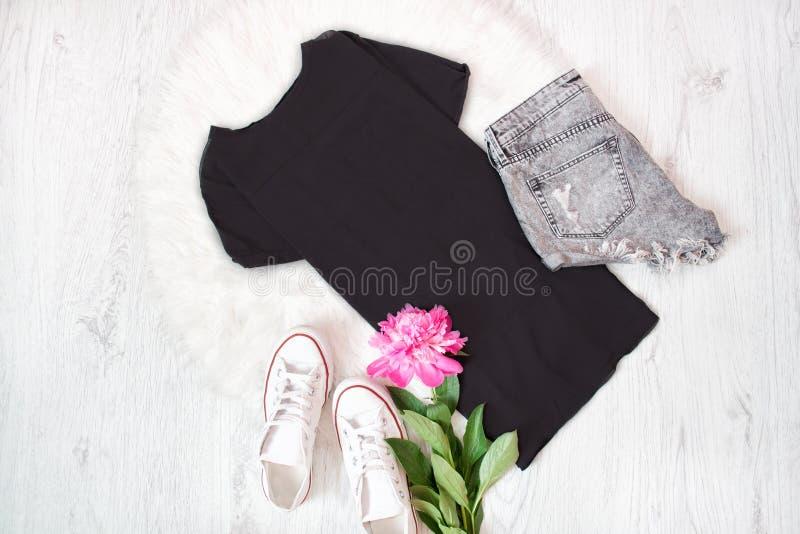Μαύρη μπλούζα, γκρίζα σορτς, άσπρα πάνινα παπούτσια και ρόδινος peony Fashi στοκ εικόνες