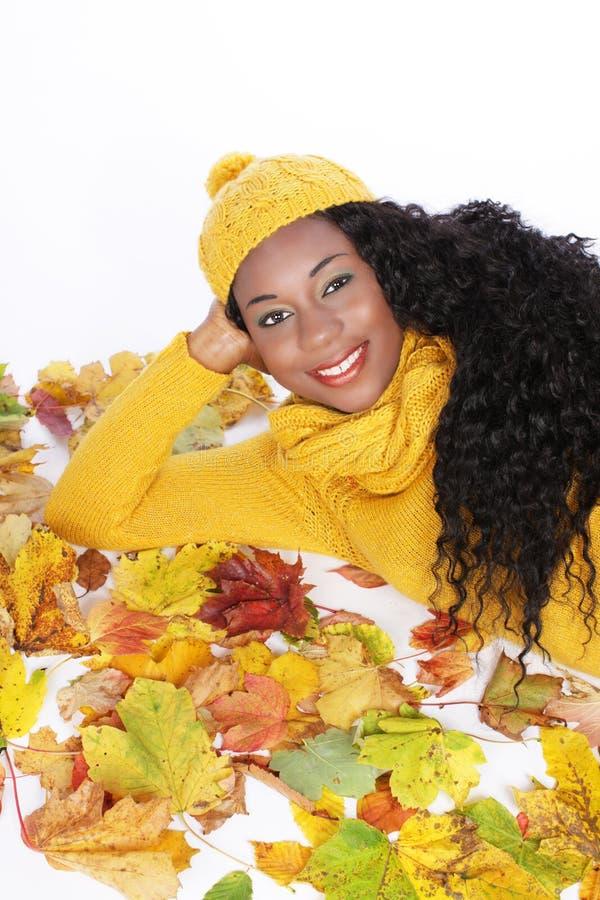Μαύρη νέα γυναίκα που βρίσκεται στα φύλλα φθινοπώρου στοκ εικόνες