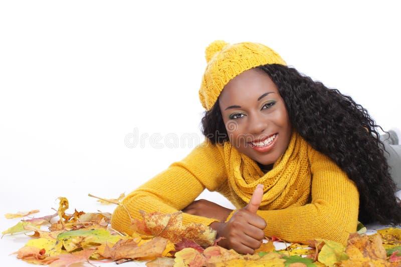 Μαύρη νέα γυναίκα που βρίσκεται στα φύλλα φθινοπώρου στοκ φωτογραφία