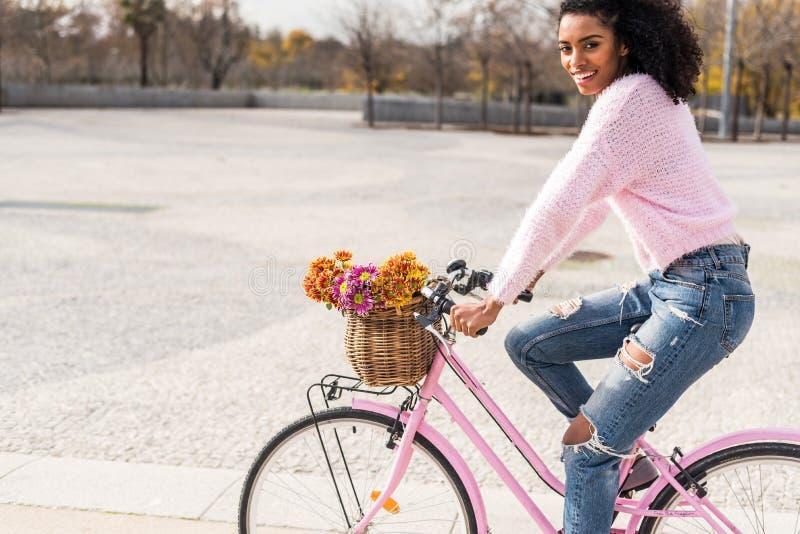 Μαύρη νέα γυναίκα που οδηγά ένα εκλεκτής ποιότητας ποδήλατο στοκ φωτογραφία