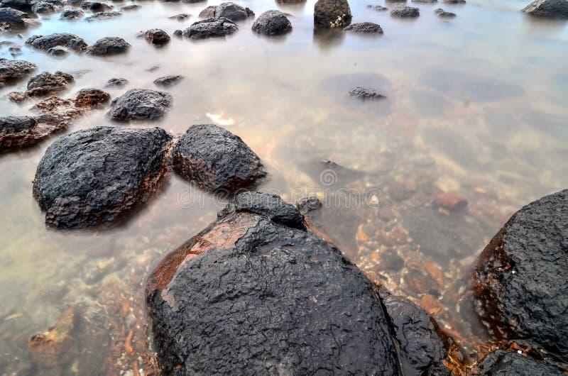 Μαύρη πέτρα στην παραλία στοκ φωτογραφίες