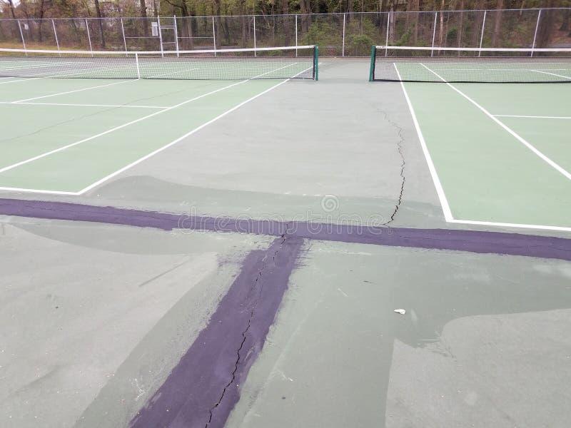 Μαύρη πίσσα για την επισκευή ρωγμών στο γήπεδο του πράσινου τένις στοκ φωτογραφία