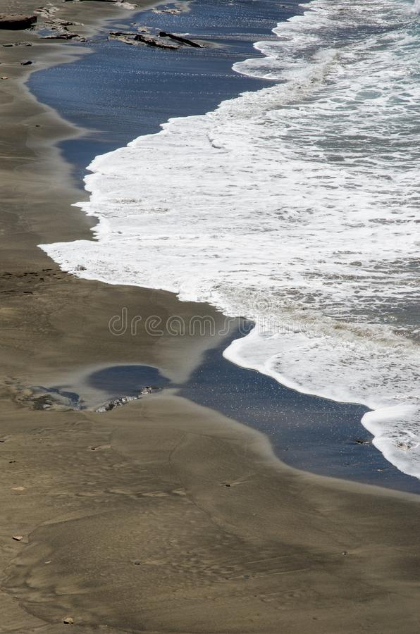 μαύρη παραλία και άσπρο κύμα στοκ εικόνα με δικαίωμα ελεύθερης χρήσης