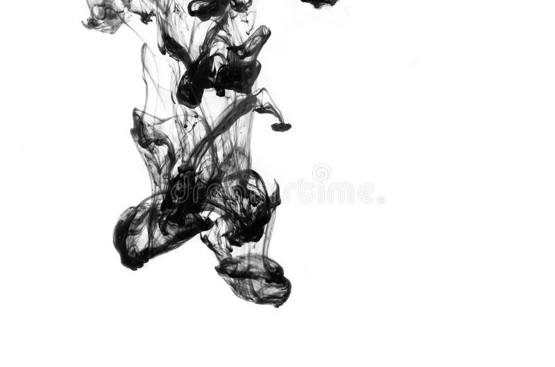 Μαύρη πτώση μελανιού στο νερό που απομονώνεται στοκ εικόνες