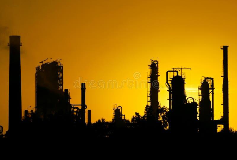 Μαύρη σκιαγραφία του σταθμού εγκαταστάσεων καθαρισμού αργού πετρελαίου κατά τη διάρκεια του ηλιοβασιλέματος στοκ εικόνα