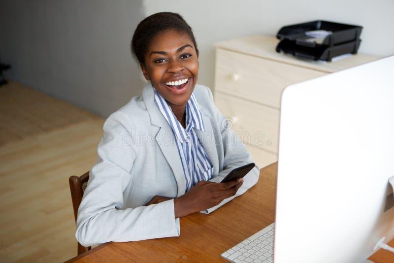 Μαύρη συνεδρίαση επιχειρηματιών στην αρχή με τον υπολογιστή και το κινητό τηλέφωνο στοκ φωτογραφία με δικαίωμα ελεύθερης χρήσης