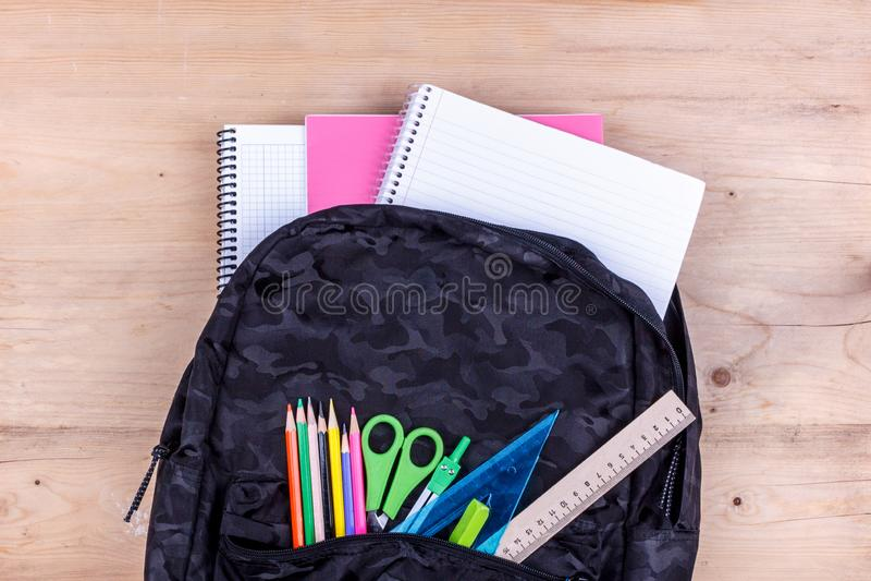 Μαύρη σχολική τσάντα με ένα σύνολο χαρτικών για το σπουδαστή και με το άσπρο σημειωματάριο σε τα E στοκ φωτογραφία