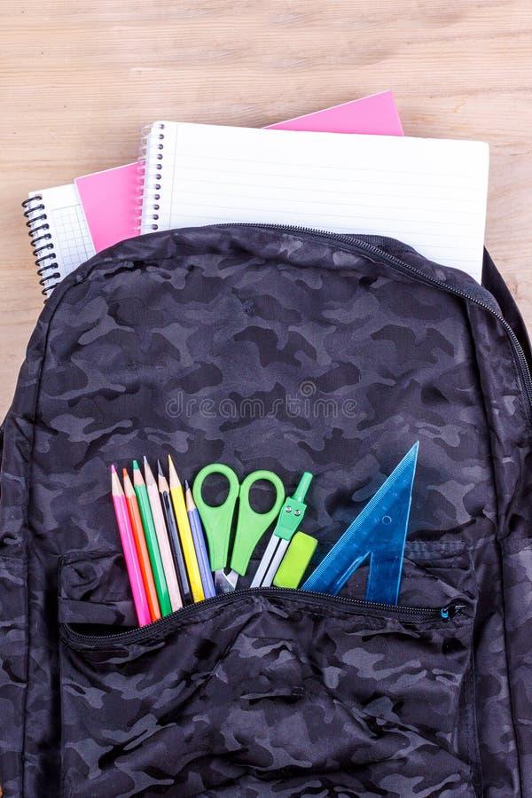 Μαύρη σχολική τσάντα με ένα σύνολο χαρτικών για το σπουδαστή και με το άσπρο σημειωματάριο σε τα E στοκ εικόνες