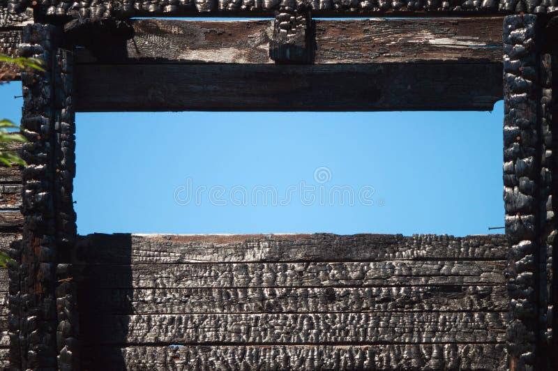 Μαύρη σύσταση άνθρακα των καψαλισμένων ξύλινων πινάκων και του παραθύρου των τοίχων σπιτιών Οικοδόμηση μετά από μια πυρκαγιά στοκ εικόνες με δικαίωμα ελεύθερης χρήσης