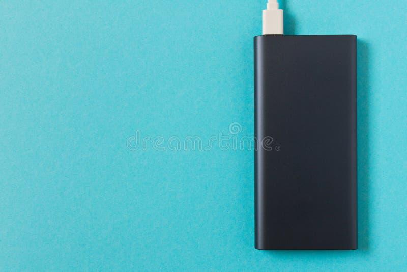 Μαύρη τράπεζα δύναμης με τον προσαρμοστή για τη χρέωση των κινητών συσκευών σε ένα μπλε υπόβαθρο στοκ φωτογραφία με δικαίωμα ελεύθερης χρήσης