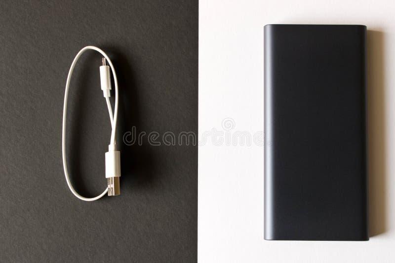Μαύρη τράπεζα δύναμης με τον προσαρμοστή για τη χρέωση των κινητών συσκευών σε ένα μαύρο άσπρο υπόβαθρο στοκ εικόνες