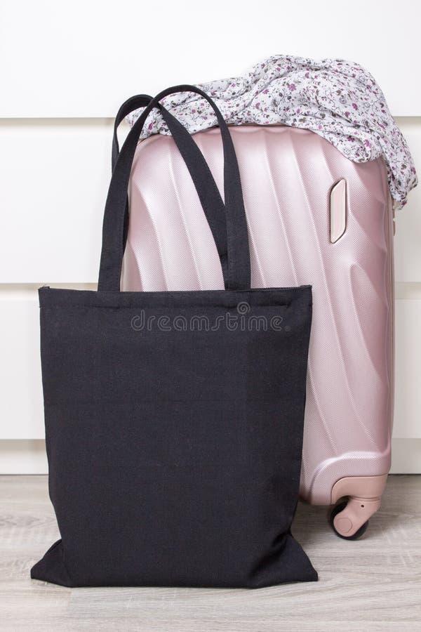 Μαύρη τσάντα eco βαμβακιού tote με μια βαλίτσα ταξιδιού, πρότυπο σχεδίου Χειροποίητες τσάντες αγορών στοκ φωτογραφία