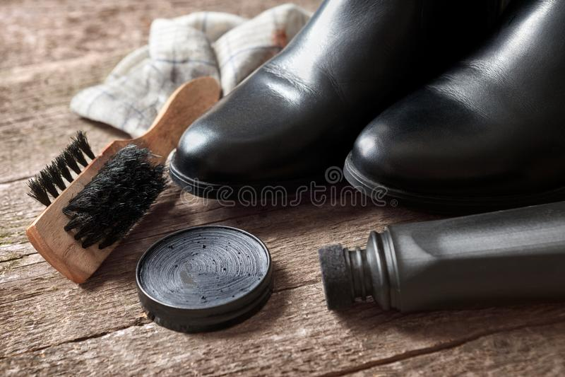 Μαύροι μπότες, βούρτσα, κρέμα στιλβωτικής ουσίας και στιλβωτής στοκ φωτογραφίες