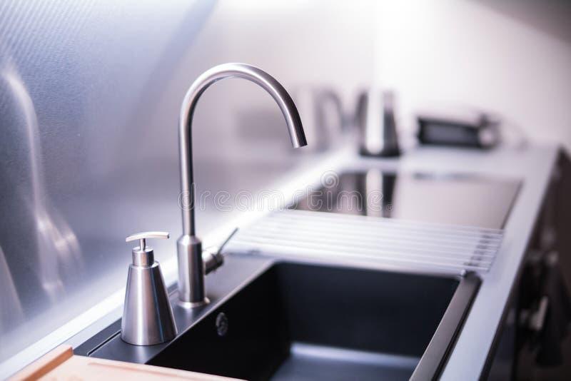 Μαύροι νεροχύτης πετρών και στρόφιγγα νερού στο νέο σύγχρονο εσωτερικό κουζινών στοκ εικόνες