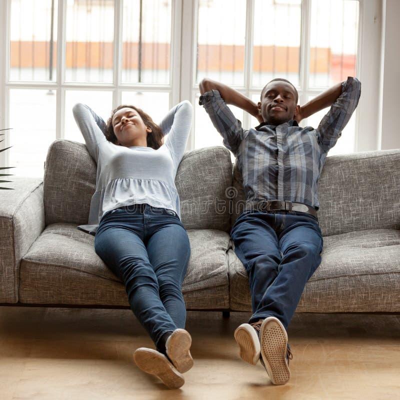 Μαύροι σύζυγος και σύζυγος που βάζουν τα χέρια πίσω από τη στήριξη κεφαλιών στοκ φωτογραφίες με δικαίωμα ελεύθερης χρήσης