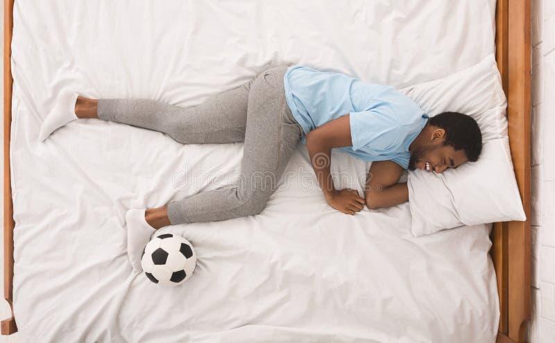Μαύρος αθλητικός τύπος με τον ύπνο σφαιρών στο κρεβάτι στοκ φωτογραφία με δικαίωμα ελεύθερης χρήσης