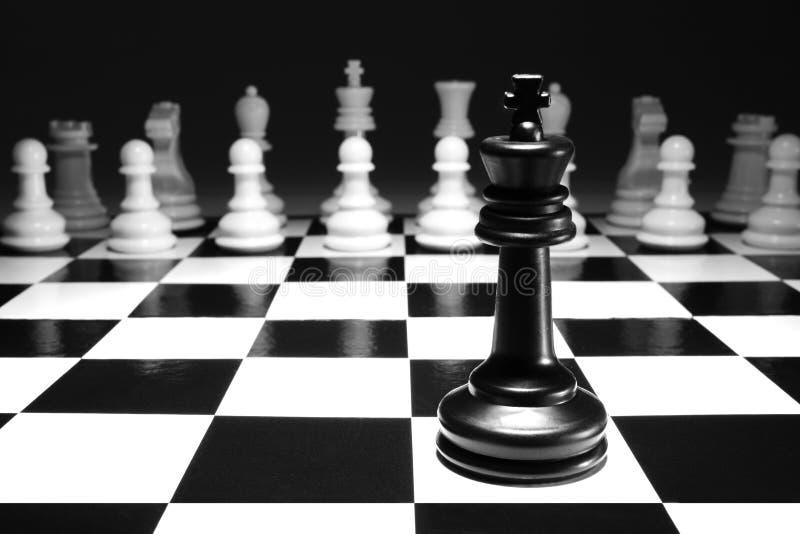 Μαύρος βασιλιάς σκακιού ενιαίος μόνο ενάντια στο άσπρο παιχνίδι ένα στρατηγικής έννοιας στρατού εκλεκτική εστίαση στοκ εικόνες