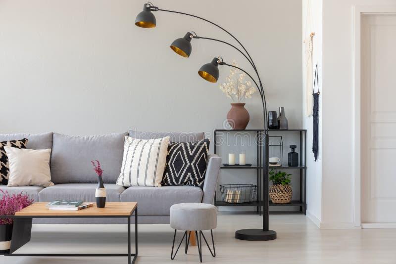 Μαύρος βιομηχανικός λαμπτήρας δίπλα στον γκρίζο καναπέ με τα διαμορφωμένα μαξιλάρια, το τραπεζάκι σαλονιού και το μαξιλάρι πουφ σ στοκ εικόνα με δικαίωμα ελεύθερης χρήσης