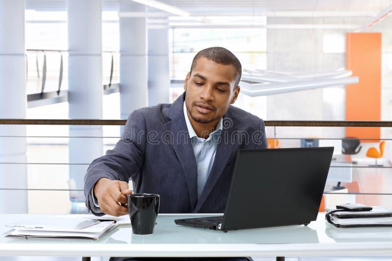 Μαύρος επιχειρηματίας που εργάζεται με τον υπολογιστή στην αρχή στοκ εικόνες