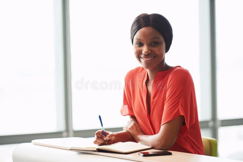 Μαύρος θηλυκός συγγραφέας που εξετάζει τη κάμερα φορώντας τη φωτεινή μπλούζα στοκ εικόνα