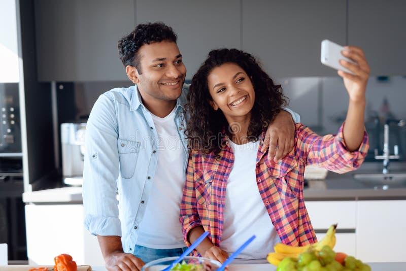 Μαύρος και γυναίκα στην κουζίνα στο σπίτι Προετοιμάζουν και κάνουν το selfi προετοιμάζοντας τα τρόφιμα στοκ εικόνες