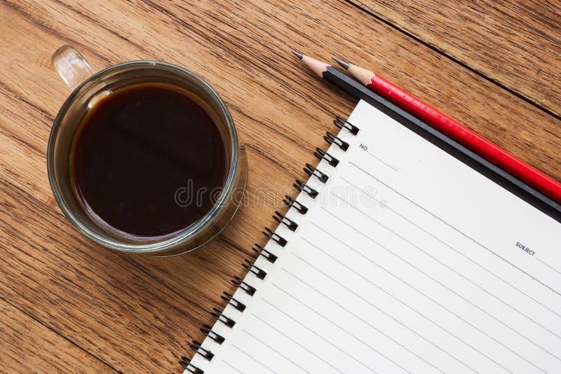 Μαύρος καφές, γυαλιά ματιών και σημειωματάριο στοκ εικόνα