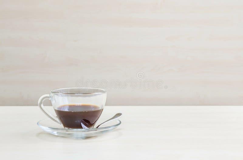 Μαύρος καφές κινηματογραφήσεων σε πρώτο πλάνο στο διαφανές φλιτζάνι του καφέ στο θολωμένο ξύλινο κατασκευασμένο υπόβαθρο γραφείων στοκ εικόνα με δικαίωμα ελεύθερης χρήσης