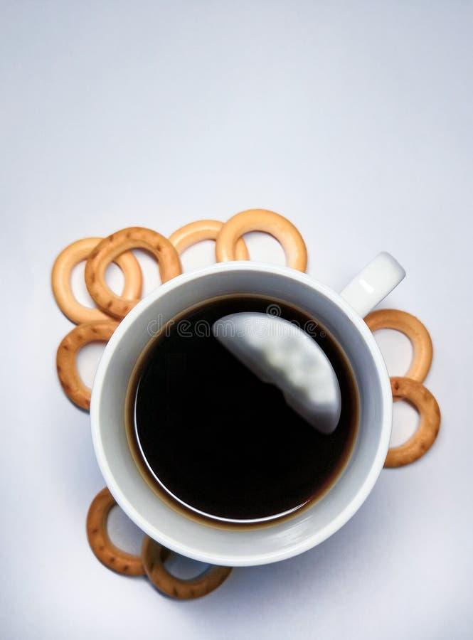 Μαύρος καφές σε ένα φλυτζάνι και μικρά bagels για το πρόγευμα σε ένα άσπρο υπόβαθρο στοκ φωτογραφία με δικαίωμα ελεύθερης χρήσης
